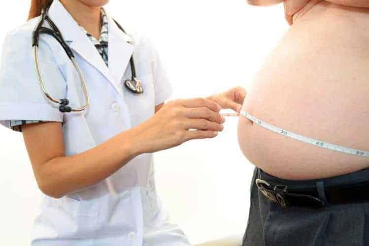 医者は肥満男の腹囲を測る