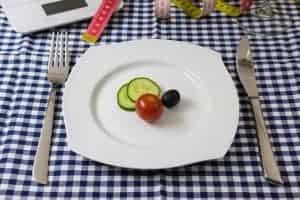 きゅうり、トマト、オリーブのスライスを皿に盛る