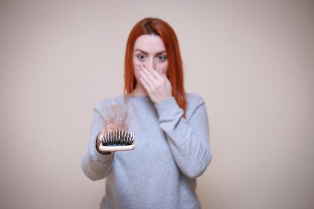 髪の毛の生えたブラシを見る女