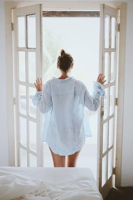 woman standing by open door