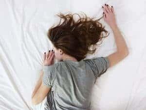 女性はベッドの上で寝る