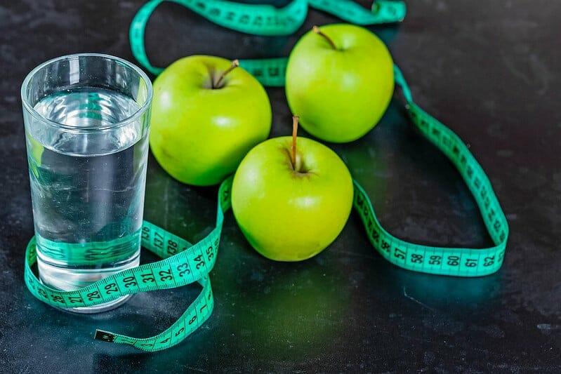 水を入れたコップと青りんごと計量テープ