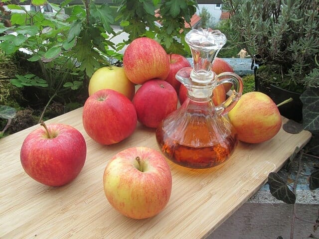 テーブルの上に置かれた新鮮なリンゴとリンゴ酢のボトル