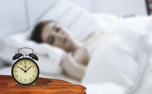 女性が寝ていると、ベッドのそばに目覚まし時計が置いてある