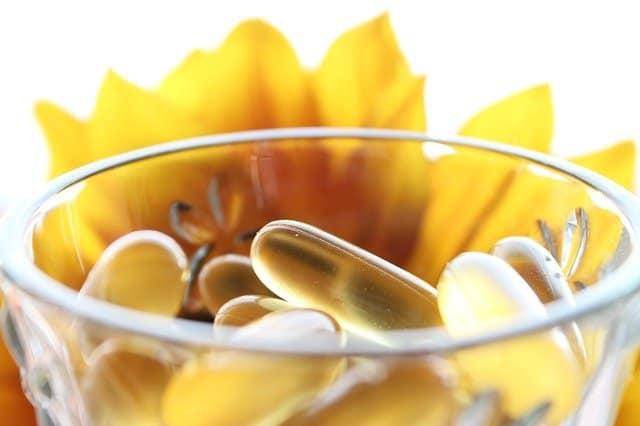 ガラスの中の丸薬、背景に黄色の花