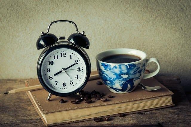 一杯のコーヒーと目覚まし時計
