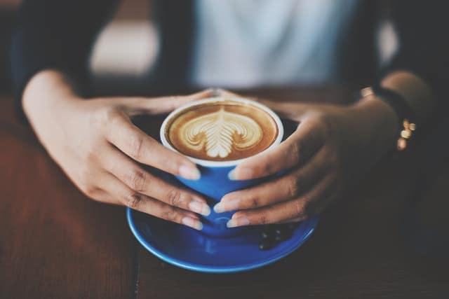 手に持ったコーヒーカップ