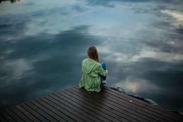 桟橋の端に腰掛けて海を眺める女性