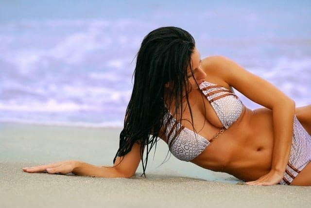 水着を着た女性がビーチに寝そべる