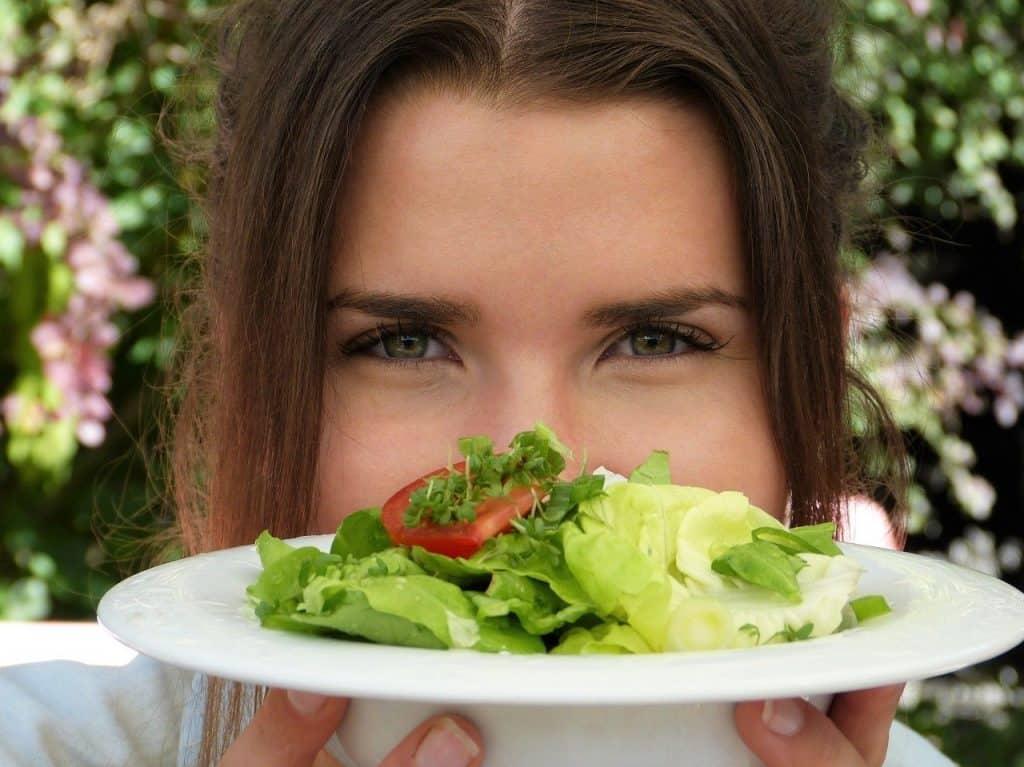 サラダの皿を持つ女