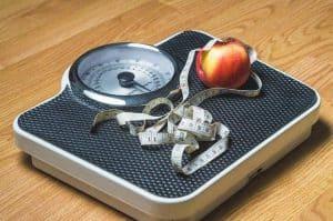秤の上のリンゴと計量カップ