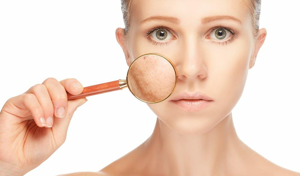虫眼鏡で自分の顔色を見る女性