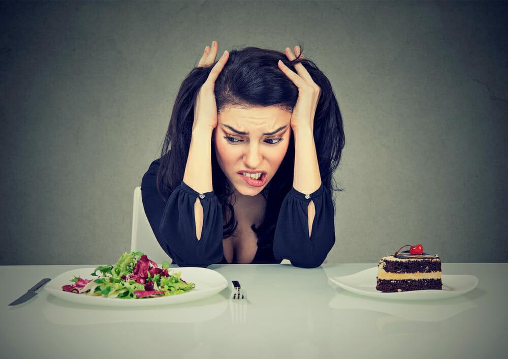 ケーキとサラダを持ってテーブルに座る女性