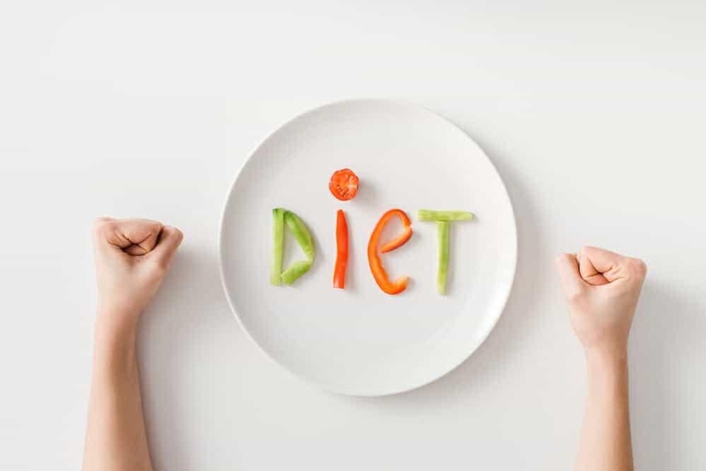 握りこぶし、お皿、お皿の上の野菜を数枚